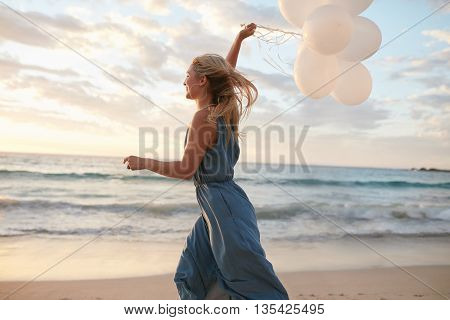 Beautiful Woman Running On The Beach With Balloons