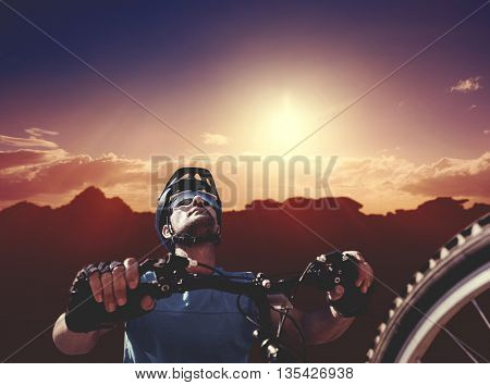Man cycling with mountain bike against composite image of landscape