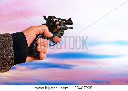 detail of hand with a handgun at sunset