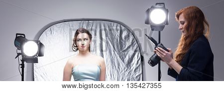 Woman photographer with camera and young fashion model during photo session panorama