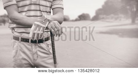 Man holding a golf club against view of a park