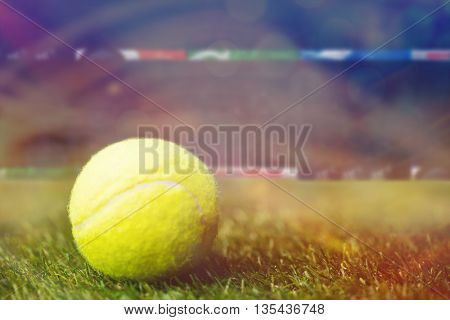 Close up of tennis ball on the grass against a stadium