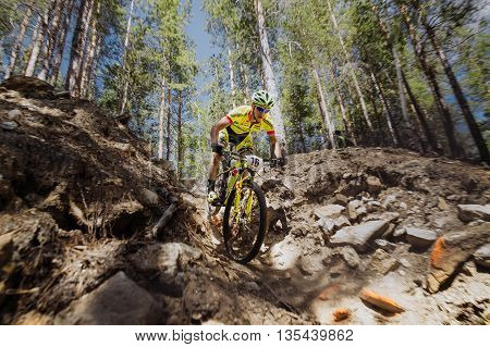 Kyshtym Russia - June 16 2016: male cyclist descends through rocks on a bike during Championship of Russia on mountain bike