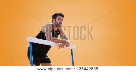 Athletic man pressed on a hurdle posing against orange background