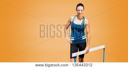 Portrait of sportswoman posing next to hurdle against orange background