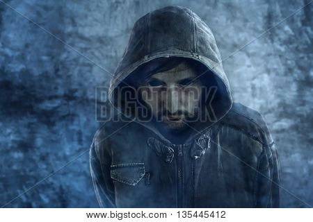 Spooky ghost appearance of dead male person with black eyes and hooded jacket