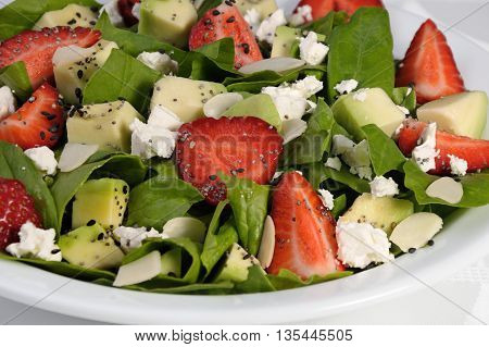 Salad spinach with strawberries avocado ricotta and sesamepoppy seeds