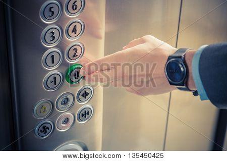 Male finger pressing the zero floor button in the elevator