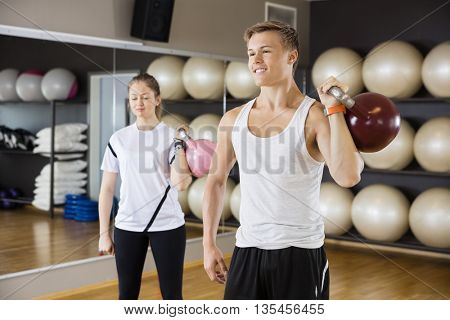 Man With Female Friend Lifting Kettlebell In Gym