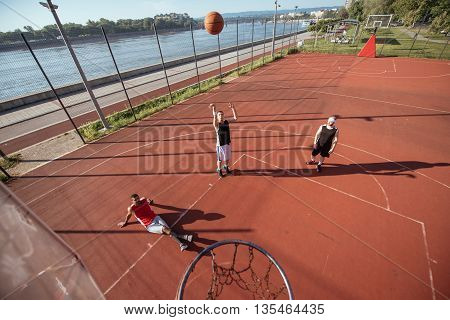 Team of basketball players playing basket outdoors.