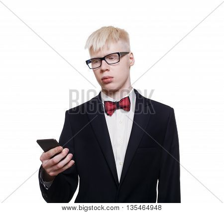 Albino young man portrait with smart phone, mobile or cell. Blond pale guy in suit with red bow tie isolated at white background. Stylish male person in eye glasses with device