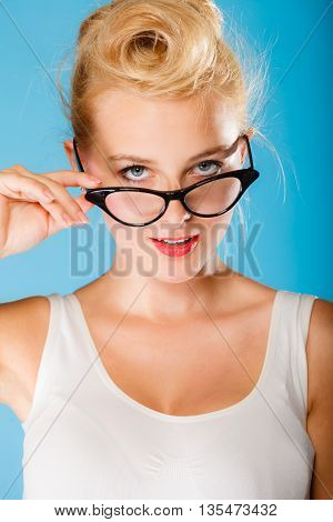 Optometrist oculist and ophthalmologist concept. Young blonde retro pin up woman with eyeglasses on blue background in studio.
