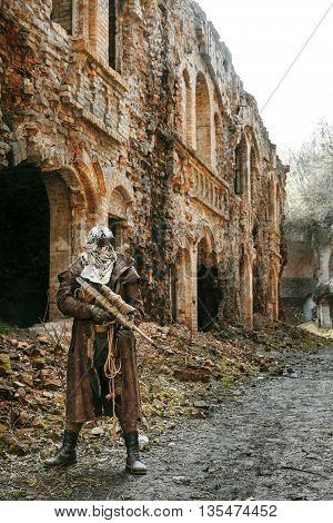 Nuclear post-apocalypse. Sole survivor in tatters and gas mask on the ruins of the destroyed city