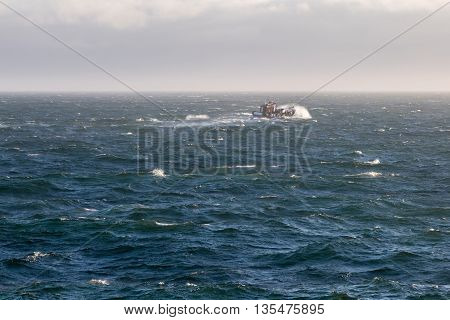 Supply boat steaming through the rough sea.