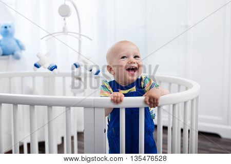 Cute laughing baby standing in a white round bed. White nursery for young children. Little boy learning to stand in his crib. Toys for infant cot. Smiling child playing with toy bear in sunny bedroom.