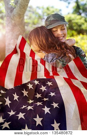 Focus on usa FLAG against happy soldier reunited with her daughter