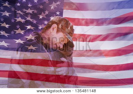 Digitally generated american flag rippling against american soldier reunited with his partner