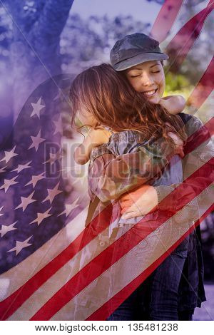 Digitally generated american flag rippling against happy soldier reunited with her daughter