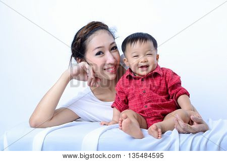 Portrait of laughing asian mother and sitting baby on bench