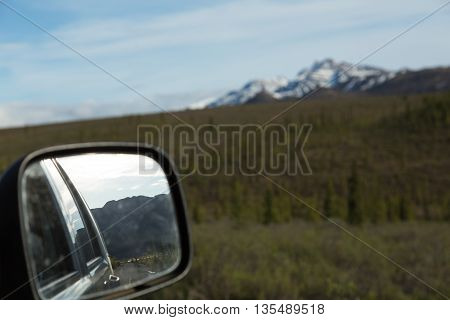 The mountains of Denali National Park reflect in an automobile mirror