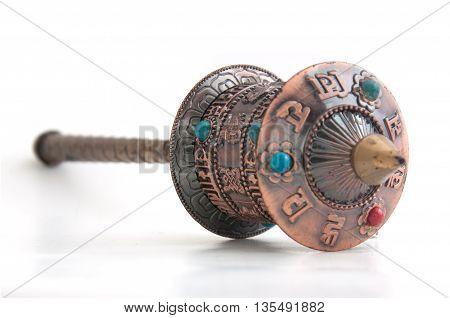 An old Tibetan prayer wheel on white background