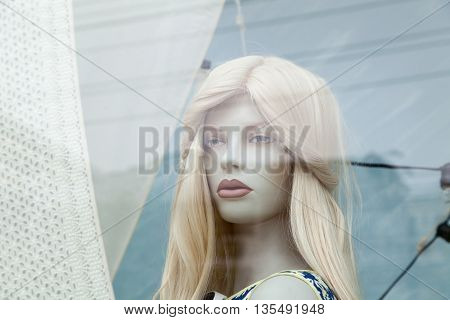 Cute realistic female mannequin face close-up in a shop window. Beautiful Caucasian manikin head with blonde hair