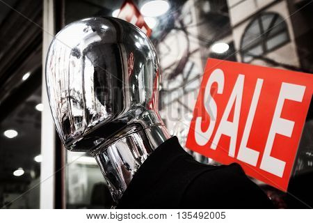 Faceless silver mannequin head dark close-up. Red sale sign