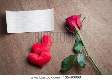 Red rose flower with blank paper and heart shape on wood background