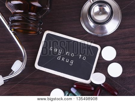 Blackboard pills and bottle with stethoscope say no to drug on wooden table with copyspace area poster