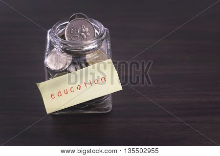Finacial concept. Money in the glass on wooden table with education word and copy space area.