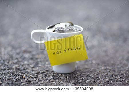 Coins in mug with vacation label blurred at background. Financial concept.