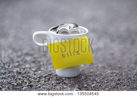Coins in mug with bills label blurred at background. Financial concept.