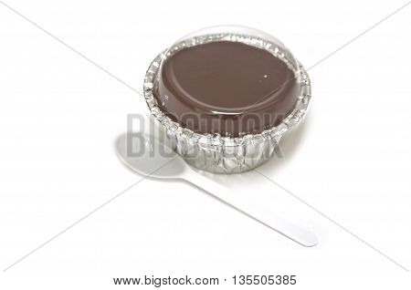 chocolate pudding and plastic spoon on white