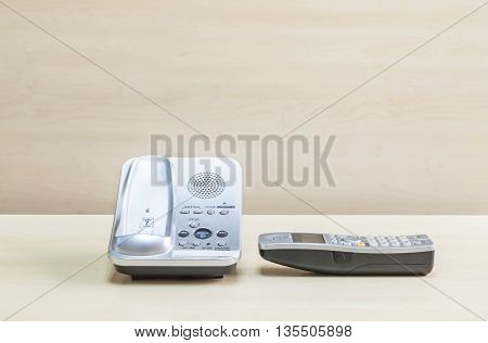 Closeup gray phone office phone on blurred wooden desk and wall textured background in the meeting room under window light
