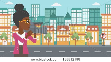 An african-american camerawoman with video camera taking a video on a city background vector flat design illustration. Horizontal layout.