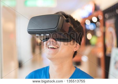 Smile happy man getting experience using VR-headset glasses of virtual reality