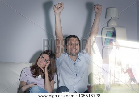Composite image of man is watching sport on television next to his bored wife at home