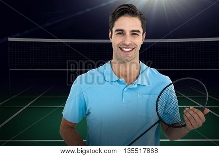 Composite image of badminton player holding badminton racket against badminton field