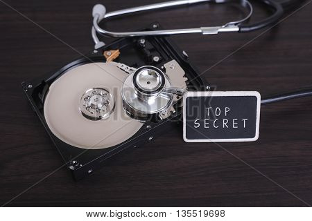 A stethoscope scanning for lost information on a hard drive disc with TOP SECRET word on board