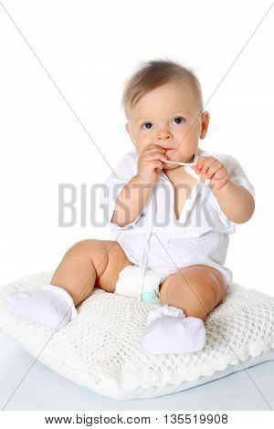 cute kid in whight blouse and diaper, the full-lenght sitting on a pillow and sucks a finger white background, isolated