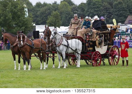 NEWBURY, UK - SEPTEMBER 21: Passengers and working crew display there preserved vintage stagecoache in the main arena for the public to view at the Berks County show on September 21, 2013 in Newbury