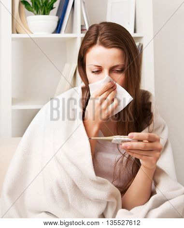 a cold girl blows her nose, and measures the temperature in a room sitting on a chair at the cabinet