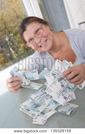 An elderly woman keeps a lot banknotes in denominations of one thousand rubles. Studio photography. Light background.