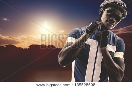 Composite image of athletic man putting his cycling helmet against landscape