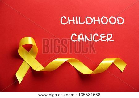 Yellow ribbon and text Childhood Cancer on red background