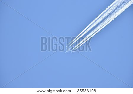 White airliner transports passengers while it pulling white contrails in blue sky