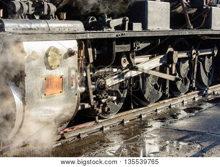 Close up of steam loco wheels with steam