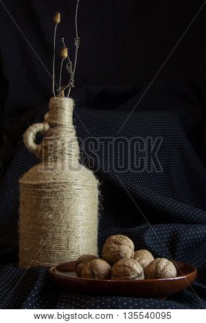 Still life of walnuts on a plate with a bottle of vintage bandaged jute and ikebana