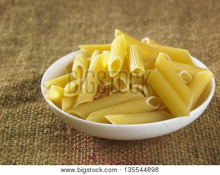 Penne pasta on top of sack cloth