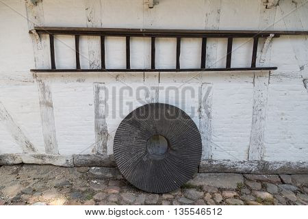 A standing millstone and hanging wooden ladder.